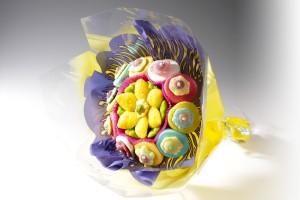 Photos d'un bouquet de fleurs en bonbons colorés, emballé dans un papier fleuriste imprimé